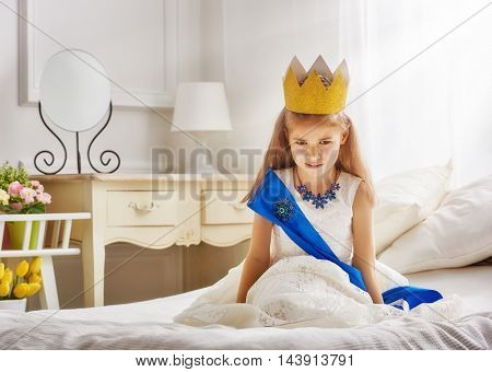 Cute little girl in a princess costume. Pretty child preparing for a costume party. Beautiful queen in gold crown.