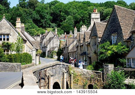 CASTLE COMBE, UNITED KINGDOM - JULY 20, 2016 - Stone bridge over the river Bybrook with cottages to the rear Castle Combe Wiltshire England UK Western Europe, July 20, 2016.