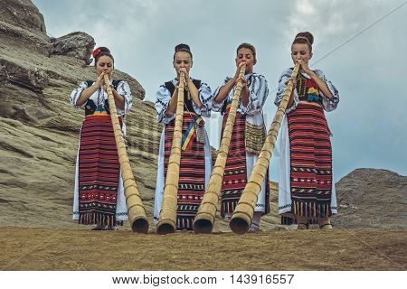 Bucegi Mountains Romania - August 6 2016: Group of Romanian female tulnic players dressed in colorful traditional costumes on Bucegi mountains plateau near the legendary Sphinx megalith.