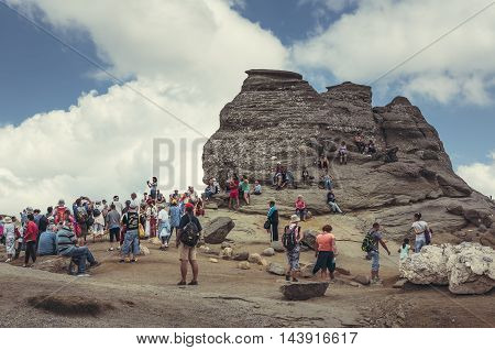 Bucegi Mountains Romania - August 6 2016: Tourists come to contemplate meditate or rest at Sphinx the legendary megalith with human face likeness located at 2216 m altitude in Bucegi Mountains.