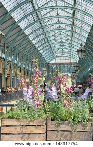 Covent Garden London England United Kingdom - August 16 2016: Central Piazza Convent Garden with Flowers in Foreground in portrait aspect