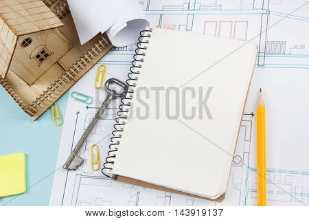 Real estate concept. Blank white notebook on architectural desk table blueprint background with key, pen, small house, office supplies. Copy space for ad text, top view