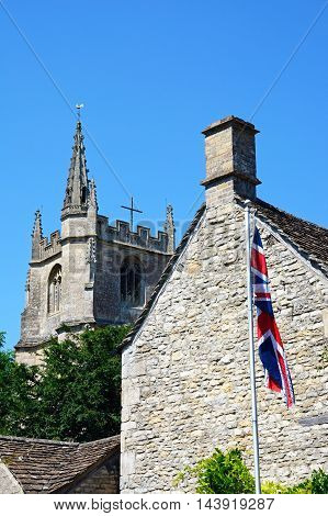 View of St Andrews church tower seen behind a cottage with the British flag in the foreground Castle Combe Wiltshire England UK Western Europe.