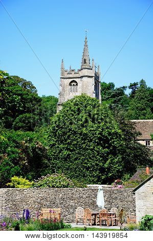 View of St Andrews church tower with a pretty garden in the foreground Castle Combe Wiltshire England UK Western Europe.