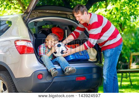 Adorable little kid boy sitting in car trunk just before leaving for summer vacation. Dad packing suitcases. Happy family going on long journey.