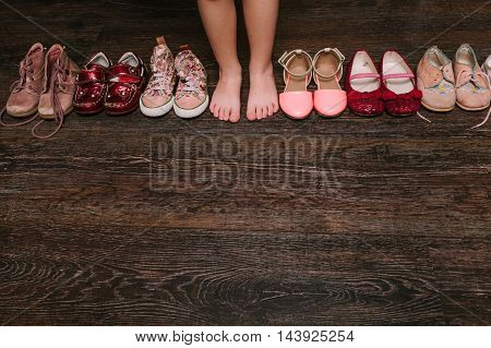 Old worn baby (child kid) shoes on the floor. sandals boots slippers top view.baby feet (legs foot). flat lay