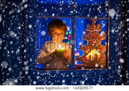 Beautiful little kid boy, standing by window at Christmas time and holding candle. Child waitng for Santa. With colorful lights from Christmas tree on background.