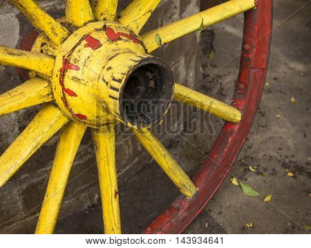 detail of old wagon wheel with metal rim in red and yellow colors