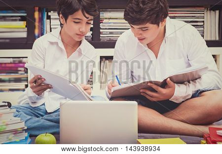 Two schoolboys in the library, best friends solving home task, thinking and discussing a difficult task, education in the high school