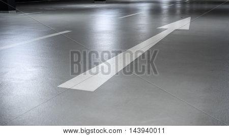 Arrow sign in a parking garage road marking