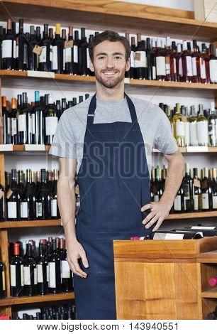 Confident Salesman Standing In Wine Shop
