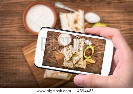 Hands taking photo chicken, avocado and vegetables burrito with smartphone.