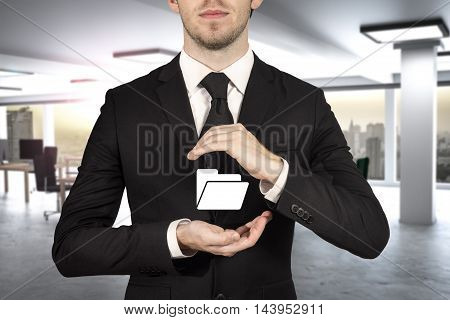 businessman in office protecting digital folder with his hands