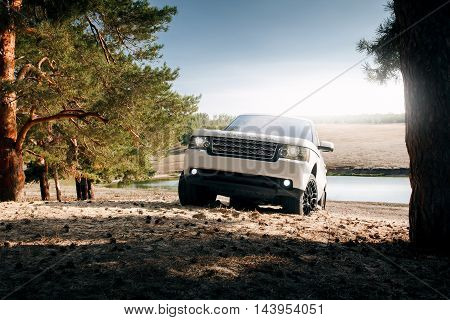 Saratov, Russia - September 01, 2014: Car Land Rover Range Rover stand on sand near lake and forest at daytime
