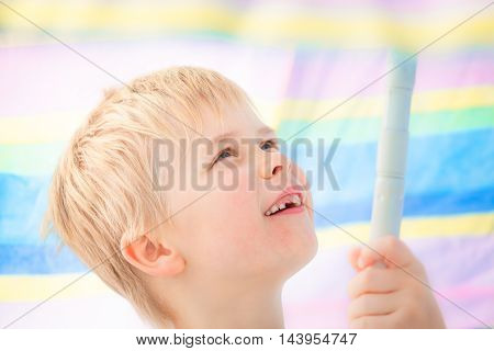 Cute child boy at school age with missing milk tooth smiling under pastel colored sunshade umbrella