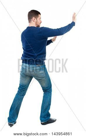 back view of business man pushes wall. Isolated over white background. Rear view people collection. backside view of person. bearded man in blue pullover shoves something on the side.