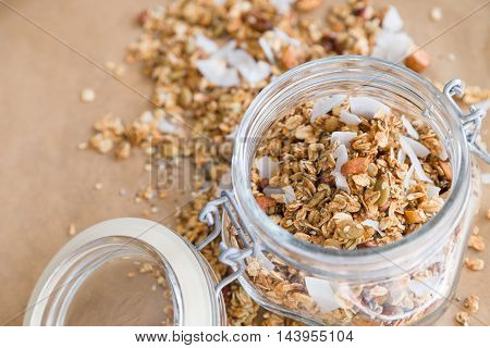 Glass jar of homemade organic granola with coconut and pecans on the baking paper background. Delicious breakfast cereal. Healthy muesli.