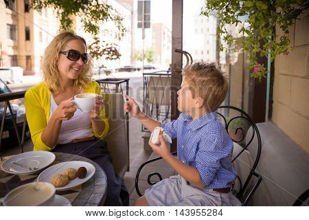 Beautiful young mother and her adorable kid boy sitting outdoors cafe drinking coffee and tea and talking. Happy two in a summer cafe terrace. Family breakfast outdoor. Mom and child eating.