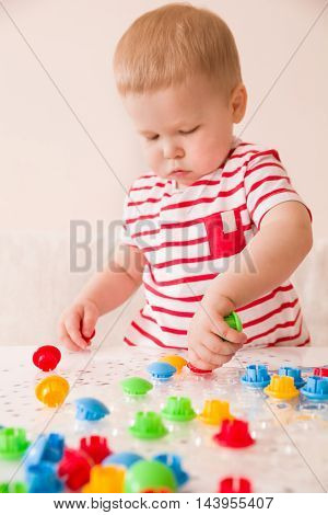 Closeup of child's hand taking bright mosaic parts. Playing and learning colors at home. Toddler boy in a striped shirt playing with colorful constructor details. Activities with children