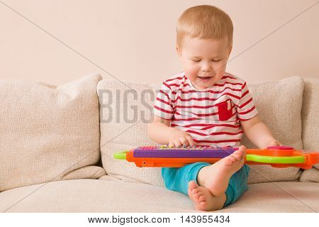 Portrait of adorable toddler boy sitting on the sofa and playing toy piano. Early learning at home. Little musician. Child and toys.Education. Indoors.