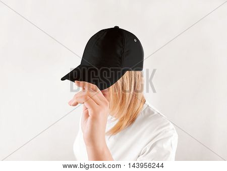 Blank black baseball cap mockup template, wear on women head, isolated, side view. Woman in clear grey hat and t shirt uniform mock up holding visor of caps. Cotton basebal cap design on delivery guy.