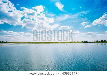 Scenic Riverine Landscape Of Skyline, River Lake Water Surface, Bright Blue Sky With White Clouds. Copyspace Background.