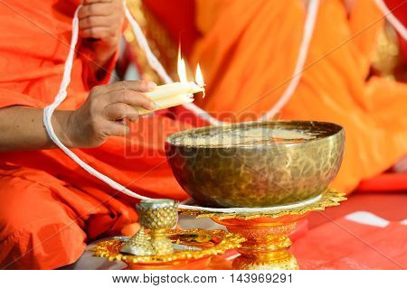 close up of buddhist monk's hand pouring melt candle tears to the water for making blessing water