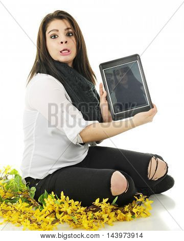 A pretty young teen sitting among forsythia, making an ugly face while holding the selfie on her ipad for the viewer to see.  On a white background.