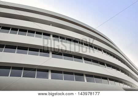 WROCLAW, POLAND - APRIL 10, 2016: Facade of a modern building of rounded shape. Curve wall with horizontal windows and white panels. Lookup. Wroclaw Poland.