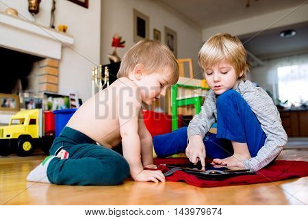 Two Boys Sitting On The Floor Playing On Tablet.