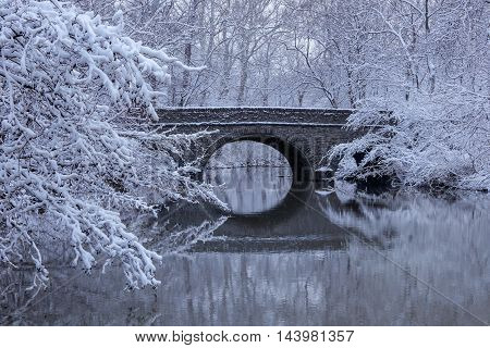 Snow covered trees framing a stone bridge reflected in the mirror - like river water during winter In the park Sharon Woods Southwestern Ohio USA