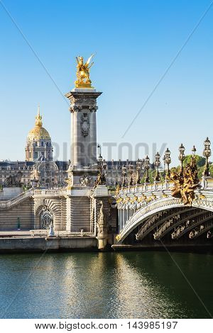 Alexandre III bridge and Hotel des Invalides in the background in the summer morning. Bridge decorated with ornate Art Nouveau lamps and sculptures.