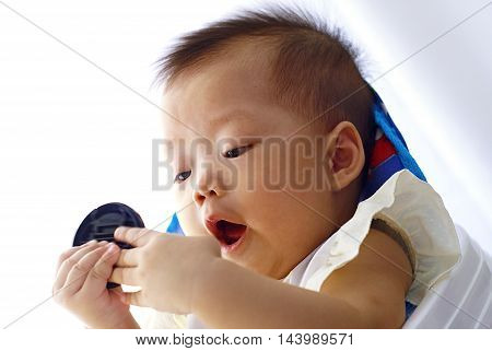 Cute Asian infant baby playing in baby walker She expressed surprise with something in her hand.