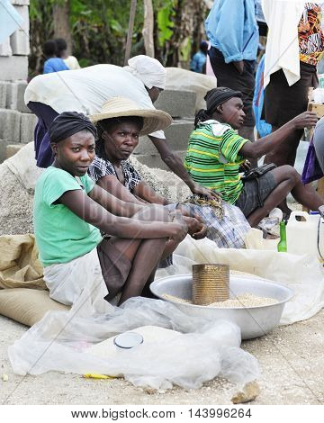 FOND BAPTISTE, HAITI - FEBRUARY 18, 2016:  Two women vendors selling grain at a rural Haitian market.  Focus on woman with large hat.