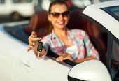 Young pretty woman sitting in a convertible car with the keys in hand - concept of buying a used car or a rental car poster