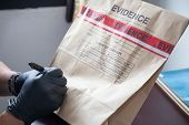 forensic 's hand in black glove writing on evidence bag and seal by red tape in crime scene investigation poster