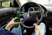 Unrecognizable man drinking and driving. Dangerous driving concept. poster