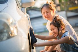 Happy Asian girl washing car with her mother at home