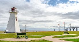 Lighthouse in the park.  Warm muggy day in PEI.  New Brunswick Confederation Bridge in distance.   A derelict lighthouse now retired to a park by PEI to New Brunswick, Inter provincial bridge in Canada.