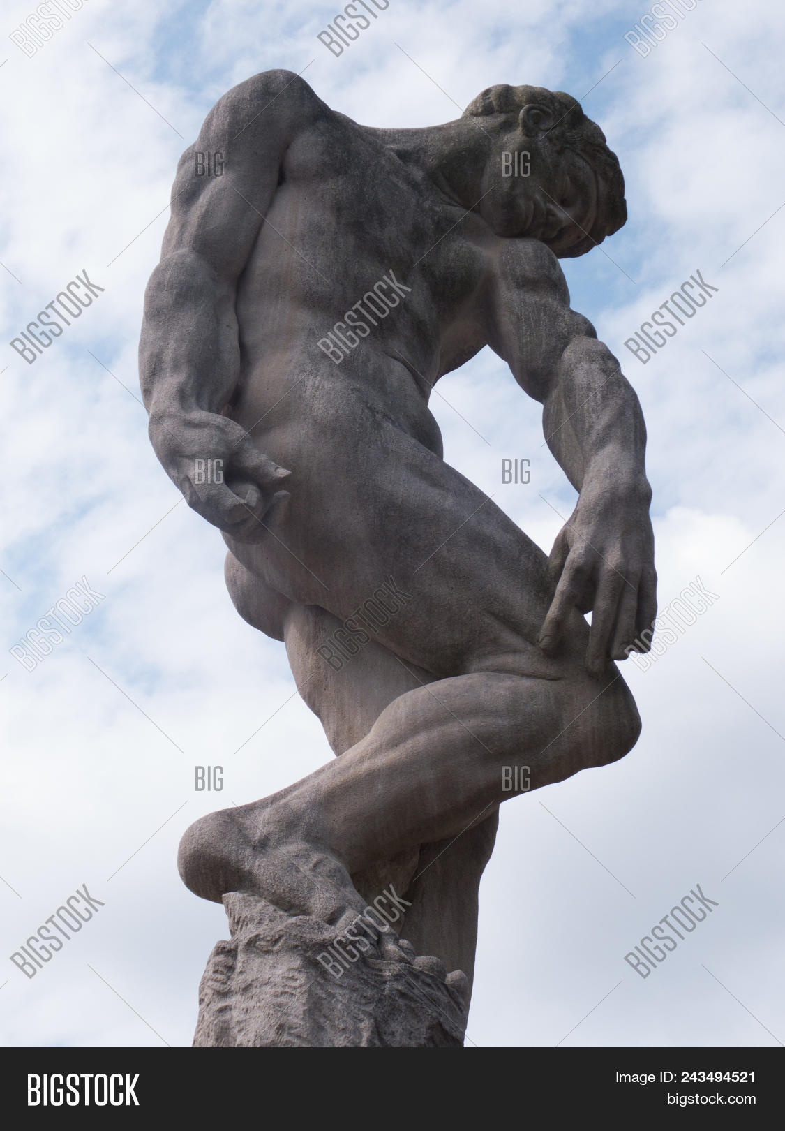 Concrete Statue Of Muscular Male Striking A Greco Roman Pose Against The Sky And Clouds