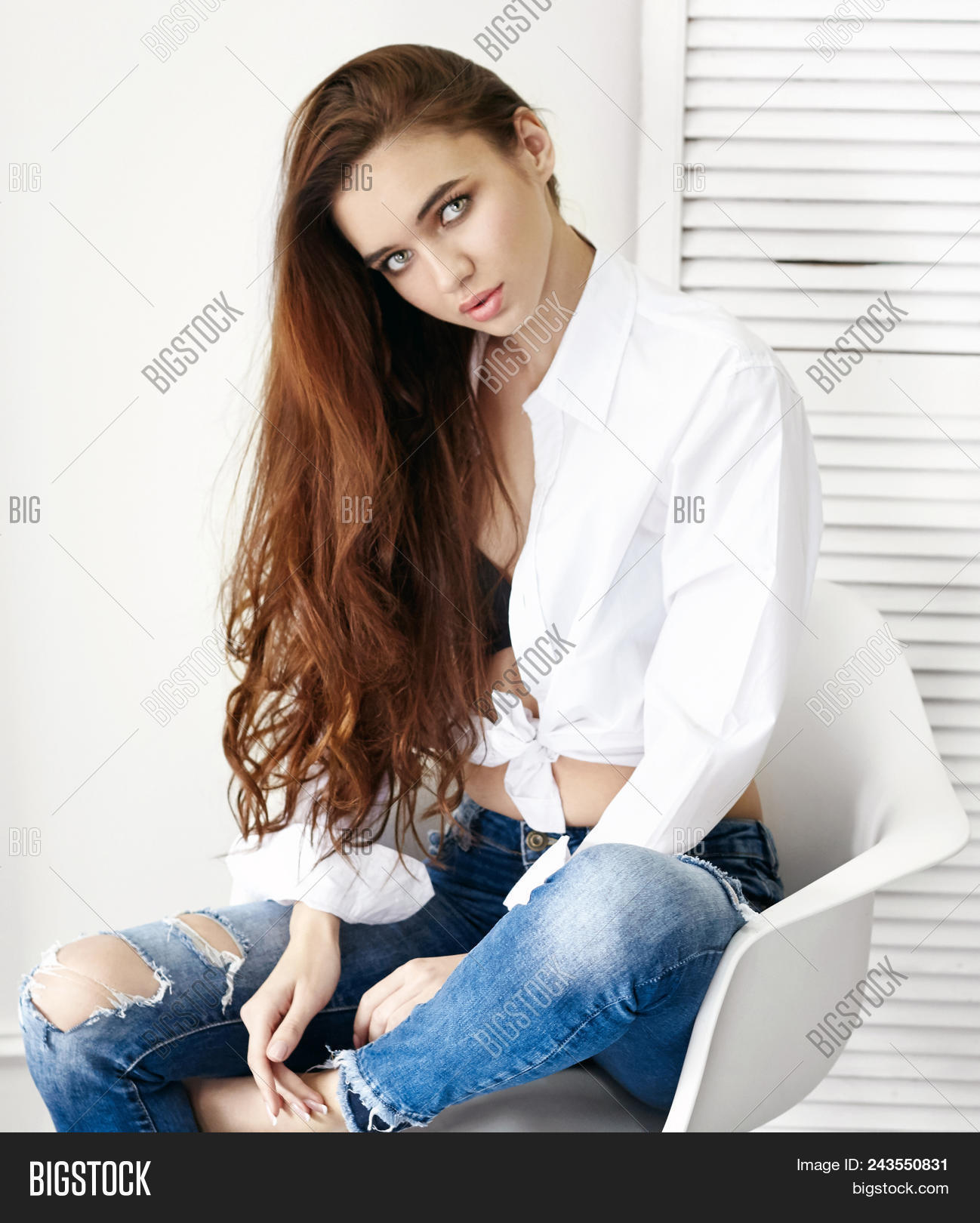 5ae75334001 Sexy Beautiful Girl In Jeans White Shirt Sitting On A Chair. Gorgeous Long  Hair And