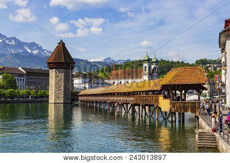 Luzern, Switzerland - April 25:chapel Bridge Famous Place On Lake Luzern With Snow Mountain Behide,
