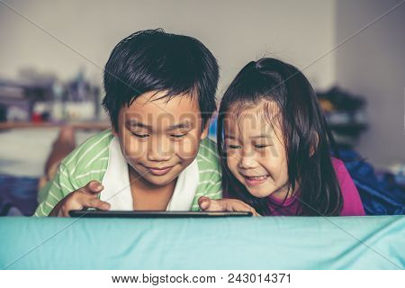 Asian Children Playing Game On Digital Tablet Together. Chinese Boy And His Pretty Younger Sister Sm