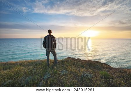 Man stands on the edge of the abyss and looks at the sea. Man relax on nature.