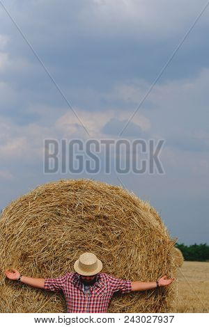 Man Resting After Hay Harvesting In Haystacks