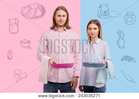Standing With Frying Pans. Relaxed Young Couple Standing With Colorful Frying Pans And Towels While