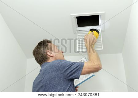 Man Inspecting Air Ducts Shining A Flashlight Through A Small Square Ceiling Vent Into Ducting Pipes