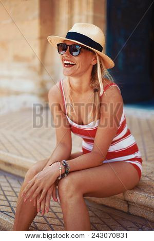 Happy Young Blonde Mediterranean Woman In Hat And Laughing, Sitting On Stairs