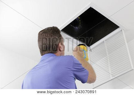 Older Male With A Yellow Flashlight Examining Hvac Ducts In A Large Square Vent. Male Technician Loo