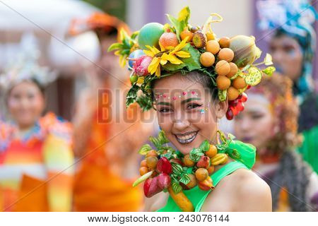 BANGKOK, THAILAND, JANUARY 17, 2018 : Portrait of a cheerful artist woman decorated with colorful plastic fruits at the Thailand tourism festival of the Lumphini park in Bangkok, Thailand